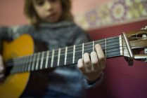 Close-up of Boy playing Spanish guitar at home — Stock Photo