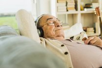 Ältere Mann liegt auf dem Sofa hören von Musik mit Kopfhörer — Stockfoto