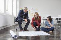 Homme d'affaires et de deux femmes au bureau en regardant le plan de construction — Photo de stock