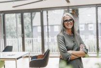Retrato de mulher sorridente com cabelos longos e grisalhos em pé no escritório — Fotografia de Stock