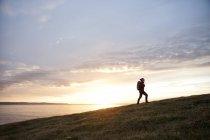 Исландия, женщина, прогуливающаяся по холму при свете фонаря — стоковое фото