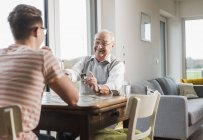 Portrait of happy senior man playing memory with grandson — Stock Photo