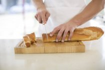 Male hands cutting baguette — Stock Photo
