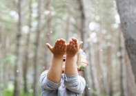Little boy catching confetti in woods — Stock Photo