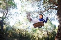Niño que se divierten en un columpio en el bosque - foto de stock