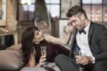 Lächelnde paar in elegante Kleidung, trinken Champagner im Bett — Stockfoto