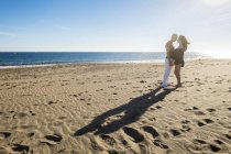 Pie feliz pareja cara a cara en la playa de la luz de fondo - foto de stock