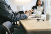 Hombre de negocios sentado en la reunión, usando laptop - foto de stock