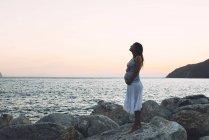 Беременная женщина, стоящая на скале перед морем на закате — стоковое фото