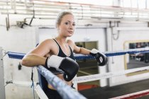 Portrait of female caucasian boxer in boxing ring — Stock Photo