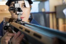 Woman with a sporting rifle aiming in a shooting range — Stock Photo