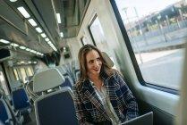 Attraktive kaukasische Geschäftsfrau im Zug mit einem Laptop — Stockfoto