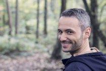 Portrait d'un homme souriant, marchant dans les bois — Photo de stock