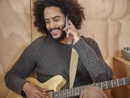 Young man with electric guitar talking on cell phone — Stock Photo