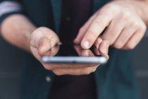 Обрезанное изображение человека, держащего смартфон с пустым экраном — стоковое фото