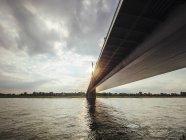 Alemania, Duesseldorf, Rheinkniebruecke sobre el río Rin en contraluz - foto de stock