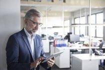 Homme d'affaires mature avec tablette Bureau — Photo de stock