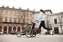 Mother running with child in stroller in the city — Stock Photo