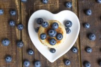 Blueberries and stack of mini pancakes on a heart-shaped plate — Stock Photo
