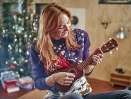 Blond woman playing ukulele in front of Christmas tree — Stock Photo