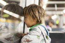Petit garçon regardant par la fenêtre du métro train — Photo de stock