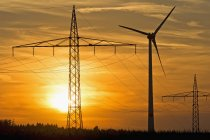 Pylônes électriques et roue à vent et soleil du soir, Bavière, Allemagne — Photo de stock