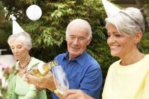 People celebrating in garden, senior man pouring champagne in glass — Stock Photo