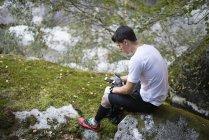 Бегун по пересеченной местности с использованием смартфона во время отдыха на скале — стоковое фото