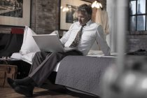 Businessman sitting on bed in hotel room and using laptop — Stock Photo