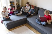 Four children on a couch using different digital devices while one boy reading a book — Stock Photo