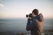 Man taking photos of the sea — Stock Photo