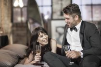 Smiling couple in elegant clothing drinking champagne in bed — Stock Photo