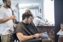Junger Mann im Friseursalon diskutiert mit Friseur — Stockfoto