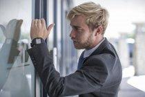 Geschäftsmann blickt durch Glastür — Stockfoto