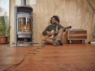 Giovane con chitarra elettrica al camino che parla al cellulare — Foto stock