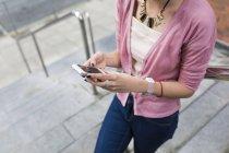 Imagen recortada de la joven chica casual caminando con teléfono inteligente en las manos - foto de stock