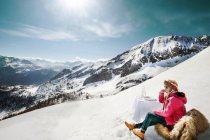 Young woman sitting at laid table in the mountains — Stock Photo