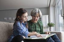 Großmutter und Enkelin zusammen mit einem Buch auf der Couch sitzen — Stockfoto