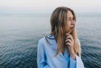 Giovane donna di fronte al mare — Foto stock