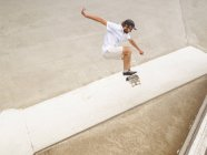 Young man skateboarding in skate park — Stock Photo
