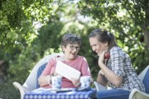 Grandmother and granddaughter in garden together looking at digital tablet — Stock Photo