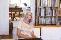 Porträt von senior kaukasischen Frau sitzt auf der Couch zu Hause — Stockfoto