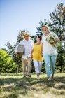 Glückliche ältere Freunde gehen auf eine Wiese mit Decke und Picknick-Korb — Stockfoto