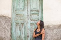 Smiling young woman outdoors leaning against a building — Stock Photo