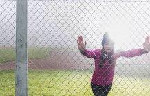 Молодая женщина, стоящая за сеткой проволоки забор делает упражнения растяжения — стоковое фото
