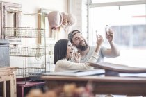Couple in antique shop looking at small bottles — Stock Photo