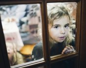 Portrait of little girl looking through a glass pane of a door — Stock Photo
