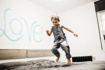 Little boy jumping on the bed at bedroom — Stock Photo