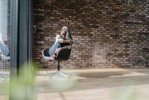 Femme avec des cheveux long gris assis sur chaise à fenêtre — Photo de stock