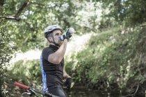 Человек на горном велосипеде в лесной питьевой воде — стоковое фото